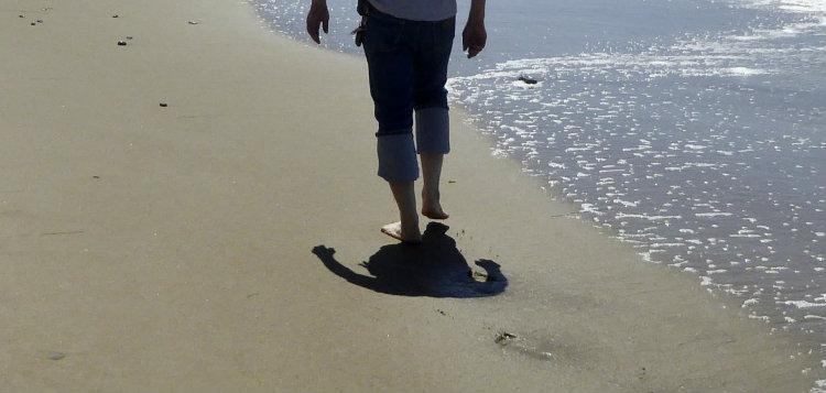 man-walking-along-beach